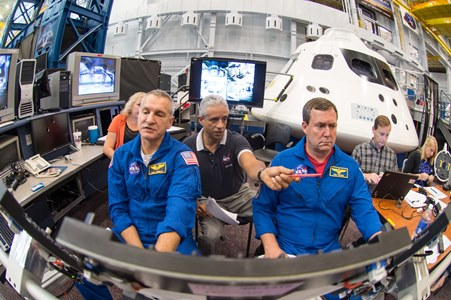 Astronauts Rick Linnehan and Mike Foreman work with simulation instructor Juan Garriga (center) to prepare for their first ascent simulation inside a mockup of NASA's new Orion spacecraft at Johnson Space Center