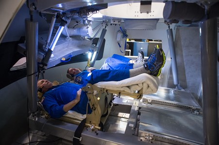 Astronauts Rick Linnehan and Mike Foreman try out a prototype display and control system inside an Orion spacecraft mockup at Johnson Space Center during the first ascent and abort simulations for the program