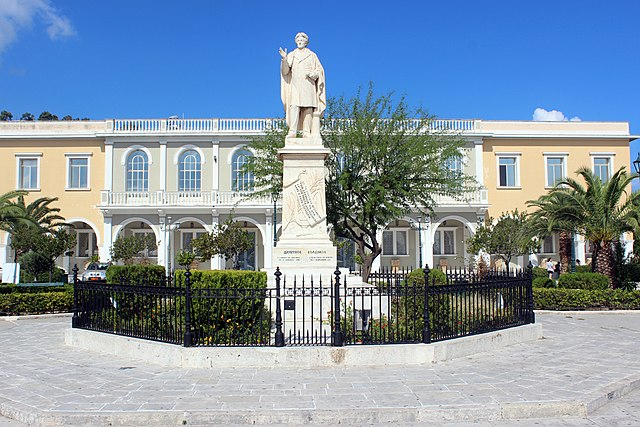 """Statue of Dionysios Solomos, in """"Solomos Square"""", in the background the Byzantine Museum, Zakynthos-Town, Zakynthos, Greek Ionian Islands. Photograghy: By Maesi64 - Own work, CC0, https://commons.wikimedia.org/w/index.php?curid=23366905"""
